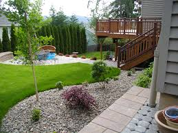Kid Friendly Backyard Landscaping Ideas For Modern House Design With White  Gravels, Green Gass And Round Outdoor Table With Chairs And Wood Bench Seat  Ideas