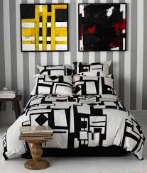 urban bedroom interior design with abstract canvas painting wall decor and comfortable black white decorative bedspread