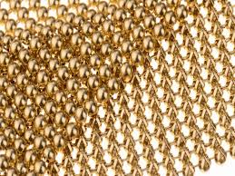 a close up picture of golden metallic fabric cloth the mesh structure is eye