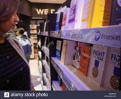 Female Shopper Browsing Books On Shelf Published By Pearson