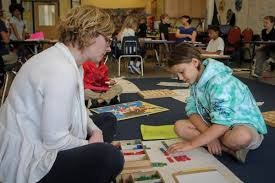 city garden montessori teacher anne lacey works with student imani palada on math problems in april 2017
