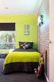 Zingy lime green wall teamed with cool exposed brick wallpaper and charcoal
