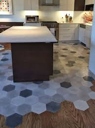 hardwood floors and grey mosaic hex tiles to separate a kitchen zone and a dining zone