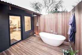 cozy outside bathroom with timber wood fence also white modern bathtub and  wooden floor