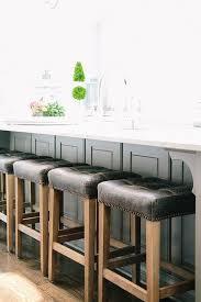 gray wainscoted center island with black tufted stools
