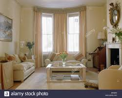 Townhouse Living Room Cream Sofas And Glass Wood Coffee Table In Traditional Cream Stock