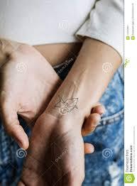 закройте вверх татуировки на запястье руки S женщины стоковое