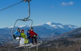a family rides the lift on a bluebird day in new hshire photo courtesy of