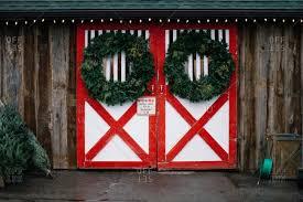 red barn doors. Green Wreaths Hanging On Painted Barn Doors Red