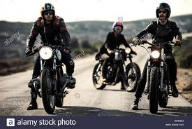 three men wearing open face crash helmets and goggles sitting on cafe racer motorcycles on a rural road