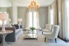 elegant light gray paneled gray and white living room features a brass 3 tier chandelier hung above a brass and lucite coffee table placed on a gray