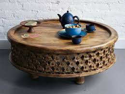 round coffee table of carved wood image and description