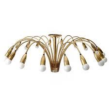 an extra large spider or sputnik flush mount light fixture made of polished brass