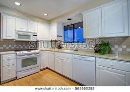 white shaker cabinets with quartz countertops. white kitchen design with shaker cabinets paired cream quartz countertops and beige