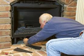 gas fireplace technician. a maan cleaning his fireplace firebox gas technician i