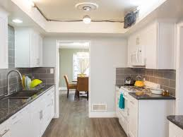 mid century modern galley kitchen and gray white color ideas and subway tile backsplash and white kitchen cabinets with black granite countertop and wood