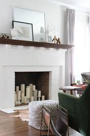 fill an unusable fireplace with diffe sized candles and holders in the same color
