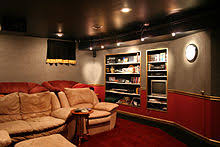 modern home movie theater. this example is of home theater screening room with video projector mounted in a box on the ceiling. built-in shelves provide place for movie decor, dvds, modern