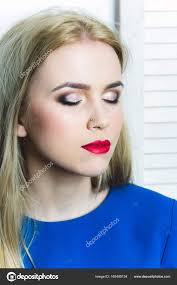 with closed eyes red lips and professional makeup on adorable face posing in blue dress woman with long blond hair on white background