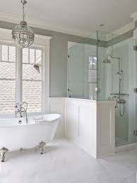 vintage inspired bathroom in neutral colors with a white clawfoot bathtub on silver legs
