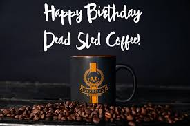 Pink flowers and coffee cup on brown grunge paper background. Happy Birthday Dead Sled Coffee