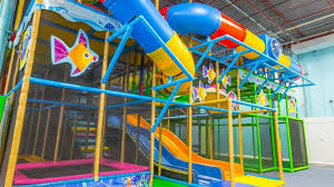 big play structure with s and slides and decorated with fish