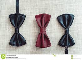 three bow ties two black and one red on a sofa team work career hipster wedding concept