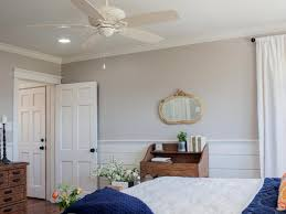 neutral country bedroom with split wall design white ceiling fan and blue accent bed covers