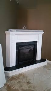 a black slate tile fireplace surround with white mantle so