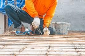 tie rebar worker rebar gridwork across a floor for strength rebar worker