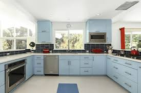 walls were knocked down to create an open chef s kitchen fitted with retro blue cabinetry complemented