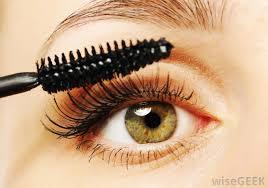 a makeup artist applies mascara to a client s eyelashes