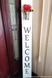 diy welcome sign propped in corner of porch by front door