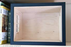 a simple picture frame encloses the front of a dolls house scale roombox which fits on