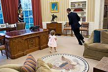 president oval office. president barack obama runs around the resolute desk in oval office n