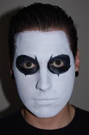 next he used one of the fine brushes to outline and fill in the shape around the eyes using the black face paint