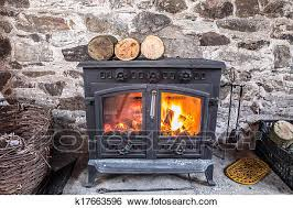 cast iron wood stove burning logs against a robust stone wall