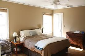 Bedroom. brown wall room with glass windows combined with brown bed sheet  with white pillow