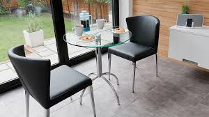 small glass table and black leather dining chairs