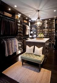 ... walk-in closet features dark stained built-ins boasting shelves over  stacked clothes rails flanking sloped shoe shelves accented with custom  lighting.