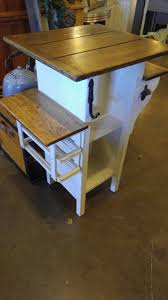 small kitchen island stand with chair rung towel bar on one side and wine rack made from a sewing machine drawer holder in the other