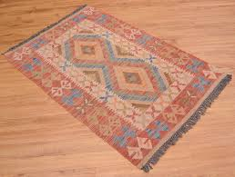 this handwoven afghan veg dye kilim rug has especially muted colours and traditional design of two