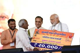 prime minister narendra modi felicitates beneficiaries of various development schemes during a public meeting in valsad gujarat on aug 23 2018
