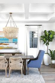 wood and woven dining chairs with gray wool rug