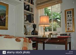 Beleuchtete Lampe Auf Antiken Tisch Vor Fenster Neben Bücherregale
