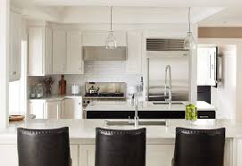 White cabinetry, marble countertops, and brick tile backsplash unify this  kitchen, with contrast