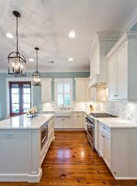 raindrop blue kitchen with white cabinets and lantern chandeliers sherwin williams