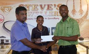 boxing board president peter abdool left accepts the cheque from mr alves in