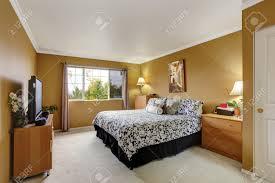 Camera da letto in color senape con pavimento chiaro moquette