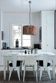 björklund covered their century old farmhouse in rural sweden in bright white paint the kitchen includes a flea market table industrial style chairs